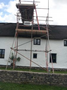 white thatched cottage with scaffolding up to chimney