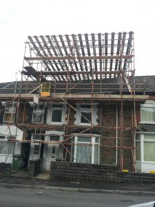house with scaffolding on for roofing repairs