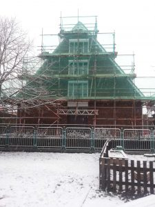 scaffolding covering house with snow on the ground